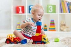 De peuter van de jong geitjejongen het spelen met stuk speelgoed auto in kinderdagverblijf stock foto's