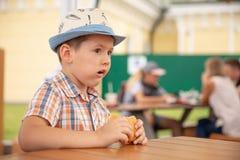 De peuterjong geitjejongen eet hamburgerzitting in kinderdagverblijfkoffie, Leuke gelukkige jongen die hamburgerzitting in het re royalty-vrije stock fotografie