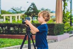 De Peuterjongen neemt beelden op een camera op een driepoot stock afbeeldingen