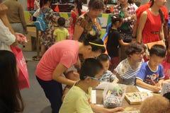 De peuterkinderen met hun Ouders in activiteiten bij kleuterschool shenzhen binnen stock afbeelding