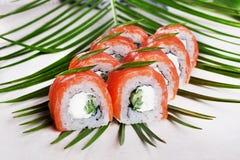 De Philadelphfia do rolo do sushi placas brancas das folhas da vida tropical ainda para o menu do restaurante Fotografia de Stock Royalty Free