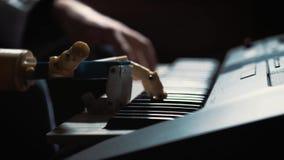 De pianist van de mensenmusicus met een prothetische hand die de piano spelen Hij speelt met twee handen, een robothand en een me