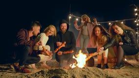 De picknick, gelukkige mensen kookt diner bij vuur en heeft pret in openlucht bij nacht stock videobeelden