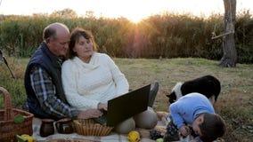 De picknick op zonsopgang, aantrekkelijk rijp paar met kleinzoon en huisdier zit bij plaid met laptop stock videobeelden