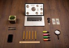 De pictogrammen van de cirkeldiagramgrafiek op laptop het scherm met bureautoebehoren Stock Fotografie