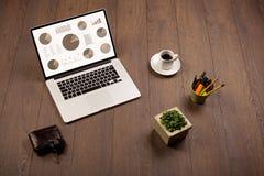 De pictogrammen van de cirkeldiagramgrafiek op laptop het scherm met bureautoebehoren Royalty-vrije Stock Fotografie