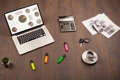 De pictogrammen van de cirkeldiagramgrafiek op laptop het scherm met bureautoebehoren Stock Foto