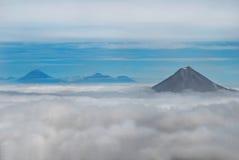 De piek van bergen boven wolken Stock Afbeeldingen
