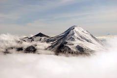 De piek van bergen boven wolken Stock Foto