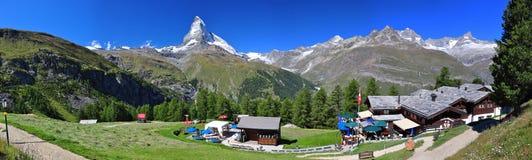 De piek van Matterhorn en een chalet stock foto