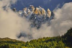 De pieken van de Aiguillesberg door wolken en blauwe hemel Chamonix, Frankrijk royalty-vrije stock fotografie