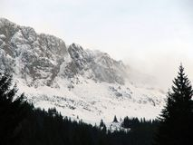 De pieken van de berg die door wolken en sneeuw worden behandeld Stock Foto's