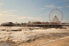 De pijler in Blackpool met grote ferris rijdt en golven stock foto's