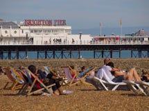 De Pijler van Brighton met mensen die op het strand ontspannen royalty-vrije stock afbeeldingen