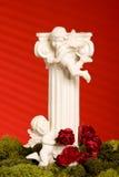 De pijler van de engel met mos op rode achtergrond Stock Afbeelding