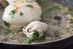 De pijlinktvis is gebraden in een pan in olie met peterselie Stock Foto's