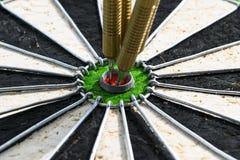 De pijltjespijl in de pijltjes van het doelcentrum in stieren` s oog sluit omhoog Het spel van pijltjes Stock Foto's