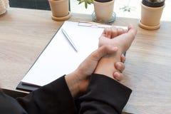 De pijn van de vrouwenhand op het syndroomconcept van het bureaubureau Stock Fotografie