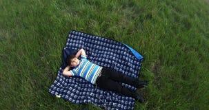 De pijnlijke jongen ligt op een deken in het midden van een gazon met groen gras en kijkt aan de hemel stock footage