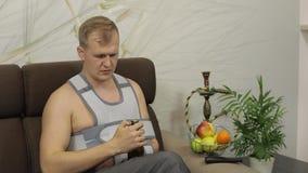 De pijnlijke mens met een gebroken wapen die de zitting van de wapensteun op een bank dragen drinkt bier stock video