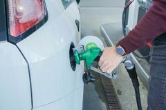 De pijp van de mensengreep om brandstof aan auto voor reis te vullen royalty-vrije stock foto