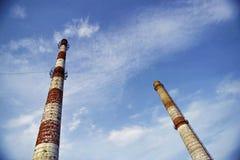 De pijpen van de baksteenfabriek op een achtergrond van blauwe hemel stock foto's