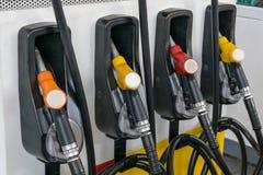 De pijpen van de pomp bij het benzinestation Stock Fotografie