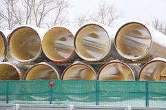 De pijpen van grote diameter liggen onder sneeuw Stock Afbeeldingen