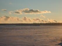 De pijpen van de raffinaderij in de haven zenden rook in de atmosfeer van de stad uit en verontreinigen de lucht royalty-vrije stock fotografie