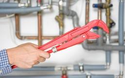 De pijpmoersleutel van de loodgieterholding met pijpsysteem in achtergrondonduidelijk beeld Stock Afbeeldingen