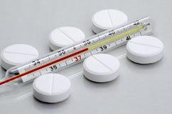 De pillen liggen naast de medische thermometer stock afbeelding