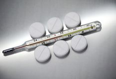 De pillen liggen naast de medische thermometer royalty-vrije stock afbeelding