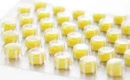 De pillen van geel die in blaren worden ingepakt die op wit worden geïsoleerd Stock Afbeelding