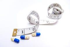 De pillen van het dieet met het meten van band Royalty-vrije Stock Foto's