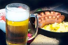 De pint van schuimend bier in a misted glas, op de achtergrond van een heerlijk diner royalty-vrije stock foto's
