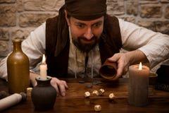 De piraat gokt met dobbelt op een middeleeuwse lijst, conceptengeluk a Royalty-vrije Stock Afbeelding