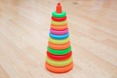 De piramide bouwt van gekleurde houten ringen met een clownhoofd op bovenkant Stuk speelgoed voor babys en peuters vreugdevol om  stock foto