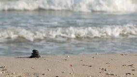 De piramide van gezoemstenen op zand, tegen de achtergrond van overzeese golven die zen symboliseren stock video