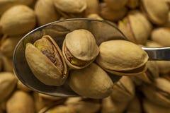 De pistaches op een lepel sluiten omhoog stock foto's