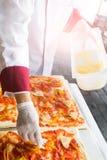 De pizza is een Italiaans die restaurant dat rond de wereld door chef-koks wordt gekookt populair is die de schotels kunnen doen  Stock Foto