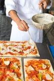 De pizza is een Italiaans die restaurant dat rond de wereld door chef-koks wordt gekookt populair is die de schotels kunnen doen  Stock Fotografie