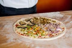 De pizza is klaar om in de oven worden gebakken royalty-vrije stock fotografie