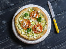De pizza met courgette, de tomaten, de uien en feta-de kaas op een licht schepen op donkere houten achtergrond in Royalty-vrije Stock Foto