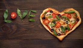 De pizza van de valentijnskaartendag in hartvorm met inschrijvingsliefde op donkere rustieke houten achtergrond Stock Foto