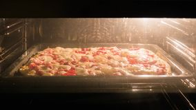 De pizza wordt gebakken in de oven in de keuken Close-up stock videobeelden