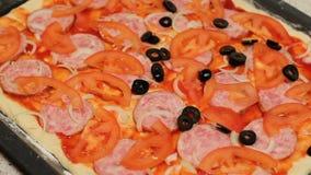 De pizzabasis Pizza het koken Gezette olijven in de pizza schik de ingrediënten in de pizza stock video