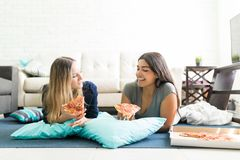 De Pizzaplakken van de vrouwenholding terwijl het Liggen op Vloer tijdens Partij royalty-vrije stock foto's