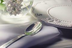 De plaat en het dessert lepelen op witte houten lijst met witte bloem in vaas Royalty-vrije Stock Afbeelding