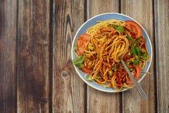 De plaat van deegwaren kruidde met kruiden, tomaten en saus op een houten lijstclose-up, vork met lange deegwaren en saus royalty-vrije stock foto