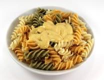 De plaat van het diner met gekleurde deegwaren en Italiaanse saus Stock Foto